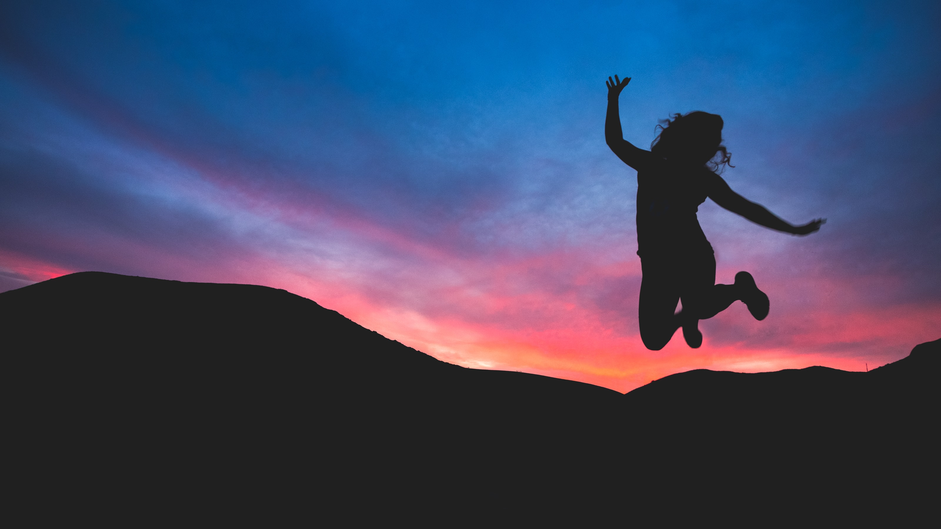Jumping woman with sunset background.